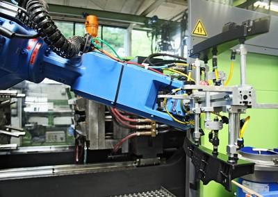 Roboter trägt Kunststoffspritzgussteil zur Sammelstädte